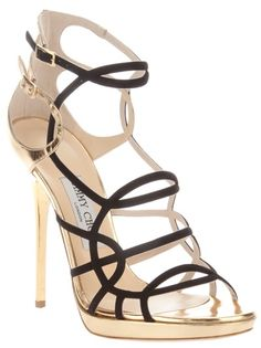 Black leather sandal from Jimmy Choo featuring a multi strap design, a contrasting gold-tone panel at the heel with a buckle fastening ankle strap, a gold-tone stiletto heel, short leather covered platform, and a leather sole.