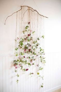 A horizontal stick w sturdy wire to hang it by, with strings tied to it that are tied to dried flowers, dangling