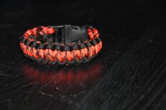 Paracord Survival Bracelet with plastic clip made from 550 paracord in orange and black. Pattern is Two Color Cobra.    Available in 6, 7 , and 8