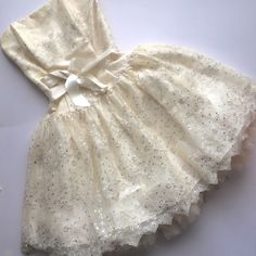 """Cache White lace sequin short bridal/prom dress Gorgeous cream lace sprinkled with sparkling sequins cover a satin bodice and skirt filled out with tulle.  Removable satin bow extenuates the waist. Size is a """"4"""" but is a very small 4 , it fits more like a 0 in bcbg or jovanni.  I am 5'3"""" and 110 pounds , 32 a cup for reference.  Adorable timeless dress .  Some of the tulle has bended up (a quick steam will fix this ) shown in 2nd picture.  Some tanning stains on inside lining (shown in 3rd…"""