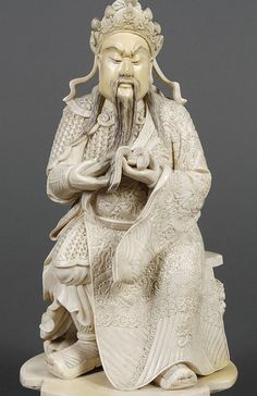"""CHINESE CARVED IVORY FIGURE OF GUAN GONG - Unusual scholarly figure of the warrior Guan Gong reading a book and seated on an elevated claw-footed dais. Clothed in an intricately woven robe with 4-toed dragons, lishui stripe and chainmail detail. Assembled from 2 carved pieces. Character mark on base. Condition good; negligible age-related cracks. Late 19th/early 20th century. 12""""H"""