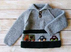 This sweater will fit baby boys up to 2 years old.  Hand knitted from soft, easy care wool blend yarn (20% wool/80% acrylic), this polo-necked pullover is heather gray with forest green stripes. Sturdy, seamless construction; raglan sleeves. Cute felt cars with button wheels speed across the front of sweater, sure to delight any toddler. Warm and practical gift for your favorite little boy.  Sweater measures 14 high, 13 across chest, and 14 1/2 from neckline to cuff.  Machine washable.