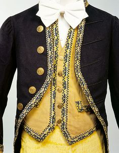 1840-60 Detail of Footman's Livery Uniform, European. Distinctive livery was a feature of male servant's dress in aristocratic households for two centuries from the Restoration of Charles ll in 1660. This livery outfit with its bold yellow colouring for the breeches and waistcoat, dates from the middle of the nineteenth century and still shows features of eighteenth century dress including the style of the coat, and the breeches. manchestergalleries.org