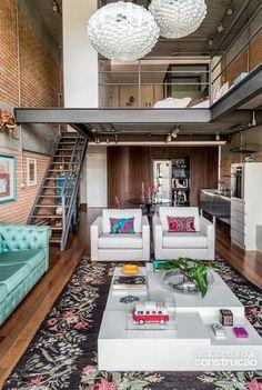 Loft com mezanino e escada em estrutura metálica, tijolos aparentes, instalações aparentes, visual super industrial