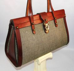 "This rare, vintage 1970 John Romain leather and tweed purse is all you'd expect from a higher-end handbag that, in its day, was the ""IT"" bag. Vintage Romain bags are collectible today, as exacting quality means these purses stand the test of time. Satchel style bag has a very equestrian, preppy, clubhouse aesthetic. Rich mahogany brown leather handles, trim and interior all contrast nicely with the woven Belgian tweed that covers the main outer body of this purse. Great brass details, ..."