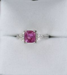 PLATINUM PINK SAPPHIRE AND DIAMOND RING  A BRIGHT PINK SAPPHIRE TWINKLES LIKE A COLORED LIGHT IN THE CENTER OF THIS FABULOUS PLATINUM RING. THE SPLENDID SAPPHIRE IS 2 35 CT AND IS COMPLEMENTED ON EITHER SIDE BY A DIAMOND TRILLION, .80 CT TW. THINK PINK WHEN WEARING THIS CLASSICALLY-BEAUTIFUL RING.  $7,450