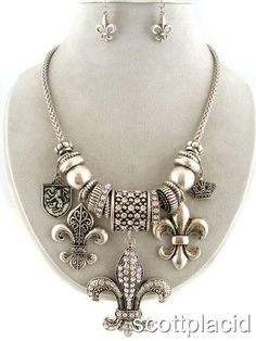 "CHUNKY FLEUR DE LIS, SHIELD, AND CROWN CHARM SILVER TONE METAL NECKLACE SET WITH CRYSTAL ACCENTS          NECKLACE: 35"" L    FLEUR DE LIS: 2.25"" L                HOOK EARRINGS                  COLOR: SILVER TONE  $27.99"
