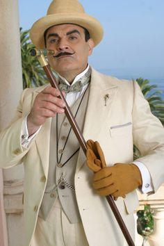 David Suchet as Hercule Poirot. Cream jacket with peaked lapel, grey vest sans lapel, patterned bow tie, cream Homburg hat and light brown gloves.