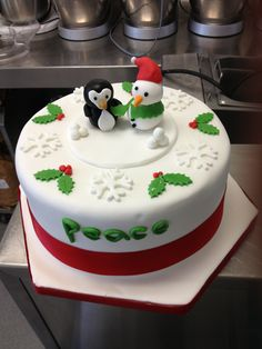 Round Christmas cake with penguin & snowman toppers and holly cut outs