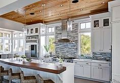 Great way of adding light into a kitchen with windows and the contrasting ceiling and island countertop keep it from feeling too sterile.
