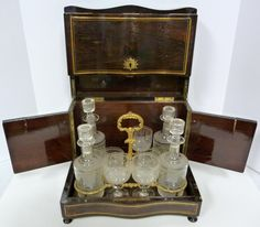 Antique French wooden inlay Tantalus set. Wood has inlay brass border and ...eliteauction.com