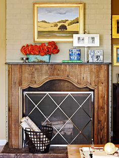 This fireplace display is made beautiful because of the details! A creamy brick background, a classy geometric screen, gild-framed art, and a splash of colorful flowers.