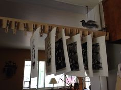 Homemade print drying rack. Wooden clothespins nailed to a 1x2 board. Hung across a doorway on hooks, it can be taken down and stored in a corner when not in use.