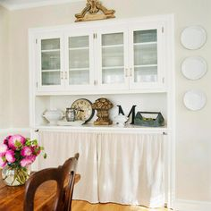 Pretty Practical  Cabinets work hard, but need not be used for function only. With crisp white woodwork and stylish glass in the original doors, the top section of this wall set stores an abundance of dishes. A tasteful skirt puts a pretty face on non-display items on the shelves below.