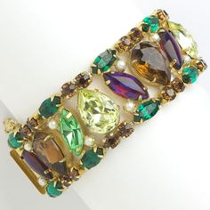 This richly-colored 1950s bracelet by Hattie Carnegie has emerald, citrine and ruby glass stones with pearls, set in gold-tone metal.