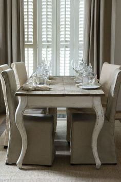 The rustic tabletop with painted legs, slipcovered chairs, linen drapes