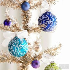 Swirls, teardrops, and tiny dots cover satin ball ornaments like frost on a winter windowpane. Freehand-paint fun patterns so each ornament is one-of-a-kind. All you need is a white paint pen and some colorful Christmas balls./