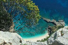 Cala Gonone Dominated By A Rocky Overhang And A Dense Forest Of Oaks This Cove Is A Strip Of Sandy White Limestone Enhanced By A Small Natural Rock