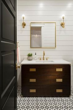 Restoration Hardware Prescott Single Extra-Wide Vanity sits on black and white mosaic cement tiles and is fitted with a white quartz countertop finished with a sink with a brass gooseneck faucet.
