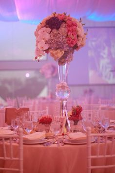 Lovely floral centerpiece, english country garden wedding. Blush pink, lavender, blue flowers in tall glass arrangement. By Jing Tanada.