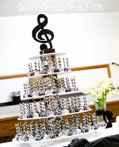 Musical cake pops on a stand, topped off with a treble clef. This design is neat for any party, wedding, or piano recital.