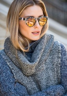 Olivia Palermo wears a gray sweater with mirrored sunglasses