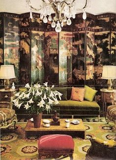 In designer Norman Norell's living room a green, black, rose and white Directoire Aubusson rug anchors a yellow green sofa and a large black Japanese screen. Rose velvet covered stool and an apricot pillow add pops of color. The crystals in the chandelier resonate with the white highlights in the Aubusson rug.