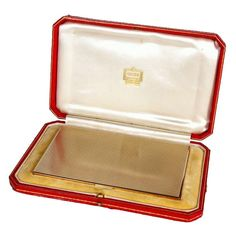 Gold cigarette case by Cartier, London.  United Kingdom.  1940s.  An exceptionally rare and beautifully-made 9 carat solid gold Art Deco-style cigarette case; manufactured by Cartier in London, c. 1940. Bearing Cartier London engraved marks as well as English 9 carat gold hallmarks, the case has its original red Cartier tooled leather and silk-lined presentation box.