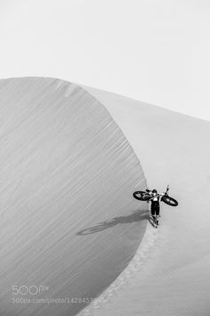 Man carrying fatbike up sand dune by shutteritch