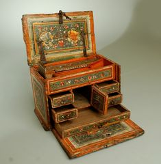 This 18th century papelera (document / writing box) from Michoacan, circa 1750, is a colonial masterpiece of the highest caliber - made by hand in the time honored tradition with the original wrought iron strapping, lock-plate, hand painted and hand lacquered surface. The hinged front and lid (both painted inside and out) opening to reveal several small compartments, cubbies and drawers. Painted on all sides with various foliate motifs in blue, green and yellow, all surrounded by a beautiful
