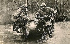 A couple German messengers cross a stream with their motorcycle & sidecar.