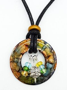 """Uniquely you! Truly a one of a kind - just like you! This is an upcycled 1.25"""" washer with corresponding earthy-colored glass beads. It was carefully made with a dazzling mix of alcohol inks in shades of blue, green, copper, and gold. The result is a beautiful, unique pendant that hangs on a 20"""" 2mm thick cotton cord with a hook and eye clasp. Please remember that colors may vary from what you see on your screen. To retain the beauty of alcohol ink pendants, please remove prior to bathing…"""