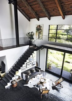 double height living space with black railings, black floors and timber ceiling. neutral with greys, blacks, whites.