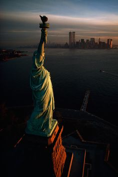 The Statue of Liberty hails dawn over New York Harbor in...