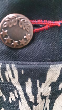 Close up of buttonhole and metal button