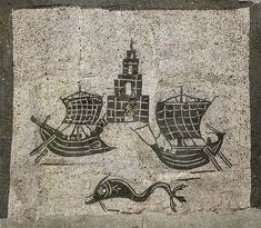 A beautifully preserved mosaic of ships and the lighthouse at Ostia Antica, with a dolphin underneath.