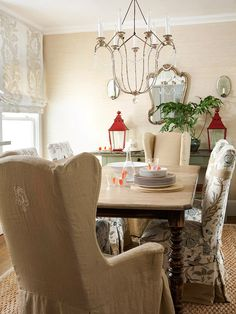 Slipcovered high backed chairs make this dining room extra cozy. Pop of red on the lanterns give a little punch to the color scheme!