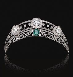 Emerald and Diamond Tiara.  Circa 1910.  The upper tier of open work trellis design millegrain-set throughout with rose diamonds, and decorated with three flower head cluster motifs set with circular-cut diamonds.  The lower tier of foliate and meander design, set with similarly-cut stones and centring on an octagonal emerald.