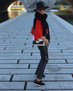 Zapatillas de deporte en blanco y negro, pantalones de piel en negro y raya en blanco y gorro en negro y gafas y jersey en rojo y chaleco de piel en negro, y bólido en blanco y negro