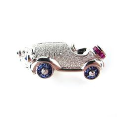White gold diamond, ruby and sapphire car brooch. White gold diamond, ruby and…