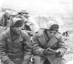 Soldiers from the 1st Cavalry Division pause to rest and collect themselves on the retreat from North Korea following the entry of Chinese communists into the war.