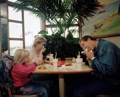Magnum photo by Martin Parr in McDonalds, Finland 1991. This photo uses the rule of thirds. Both vertical lines run along the heads of both the male and female and the second horizontal along the edge of the table.