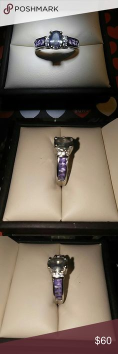 MYSTIC TOPAZ., AMETHYST & CZ SET IN 18K WHT GP Center stone is 1/4 ct. wt. mystic topaz with 3 zirconia stones on each side & 8 baguette cut amethyst gems. 4 set on each side of the band. All. Set in 18K white gold plated sterling silver. Absolutely Beautiful!! N/A Jewelry Rings