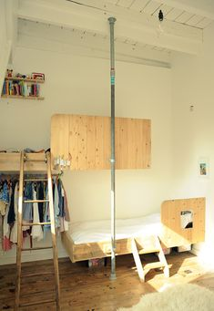 Kee klamp floor-to-ceiling pole to give wall mounted beds extra support. Kee klamp hanging rail under bed for extra storage. Genius!