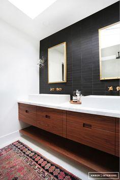 Downstairs bathroom idea: salvaged dresser, double sinks in white, black tile backsplash, gold silver target mirrors, colorful rug, white tile everywhere else, original Fir floors