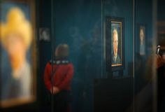A visitor walks past a self portrait of Dutch Post-Impressionist painter Vincent van Gogh on the ground floor of the Vincent van Gogh museum on November 25, 2014 in Amsterdam, Netherlands. The new presentation of the permanent collection of Vincent van Gogh (1853-1890) works focuses on the development of the artist and the myths surrounding Van Gogh's suicide, illness and ear are discussed in detail for the first time at the museum. On the ground floor of the museum, visitor's first walk ...