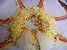Bacon, Egg, & Cheese in crescent rolls   can of crescents 8 count,5 large eggs   1 cup of shredded Colby and monterey jack cheese ,8 slices of fully cooked bacon. Preheat oven to 375 F degrees.  Scramble your eggs on stove top.  Lay out crescents  on a parchment lined pizza pan.  Looks YUMMY! I used 6 medium sized eggs. i might do more next time like 8 eggs.