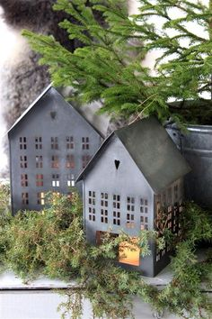 Tiny tin houses with candles and evergreens for the winter holiday