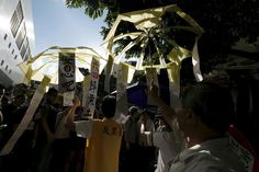 TIANANMEN-ANNIVERSARY/ Pro-China supporters carry torn yellow umbrellas, mocking the pro-democracy Occupy Central movement, outside Victoria Park in Hong Kong, China June 4, 2015. Tens of thousands of people are due to attend an annual candlelight vigil at the park in Hong Kong on June 4 to mark Beijing's Tiananmen Square crackdown in 1989, as tension lingers in the financial hub from its pro-democracy protests last year. REUTERS/Bobby Yip