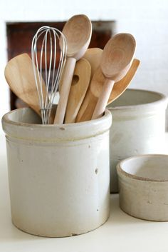 use antique crocks to hold kitchen utensils